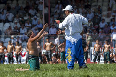 A wrestler pleads with a referee at the Elmali Turkish Oil Wrestling Festival in Turkey. Stock Images