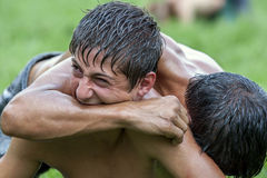 A wrestler sinks his teeth into his opponents arm at the Kirkpinar Turkish Oil Wrestling Festival in Edirne in Turkey. Royalty Free Stock Photography