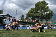 Wrestlers battle for victory at the Kemer Turkish Oil Wrestling Festival in Turkey as a storm approaches overhead. Stock Photography