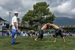 Wrestlers battle for victory at the Kemer Turkish Oil Wrestling Festival in Turkey as a storm approaches overhead. Stock Photos