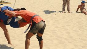 Wrestlers the duel on a sandy beach stock video footage
