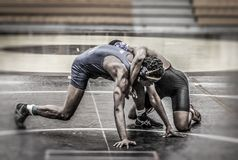 The Wrestlers - Grappling for Victory. Two wrestlers getting to grips with strength, speed and technique in a match royalty free stock photo