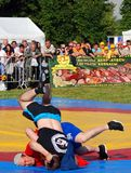 Wrestlers in the ring. MOSCOW - JULY 18, 2015: Wrestlers in the ring. A dramatic moment of the competition - two men fall on the ground. Sabantui celebration in Stock Image
