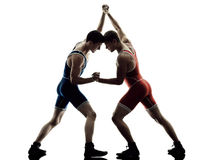 Wrestlers wrestling men isolated silhouette. Two caucasian wrestlers wrestling men on isolated silhouette white background Royalty Free Stock Photos