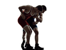 Wrestlers wrestling men isolated silhouette. Two caucasian wrestlers wrestling men on isolated silhouette white background Royalty Free Stock Photography