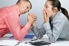 Wrestling. Man and woman in arm wrestling gesture on working table during meeting royalty free stock photos