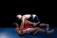 Wrestling. Mens wrestling action. Studio shot over black Stock Photography