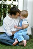 Wrestling with Dad. Father and son sit barefoot on the grass. Boy has on overalls and white shirt. Dad has on white shirt and jeans stock photography