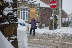 Woman struggling in snowy blizzard to cross a road. stock image