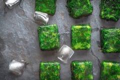 Würfel des gefrorenen Spinats mit Eiswürfeln auf der Steintischplatteansicht Lizenzfreie Stockfotos