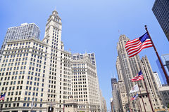 Wrigley Building and Tribune Tower on Michigan Avenue with American flag on the foreground in Chicago Stock Photos