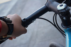 Wrings hands on the handlebars of the bike. Stock Photos