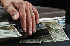 Wrinkle senior hand touch suitcase full of dollar cash Stock Image