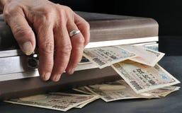 Wrinkle senior hand touch suitcase full of Yen cash in dark room Stock Photos