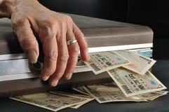 Wrinkle senior hand touch suitcase full of Yen cash in dark room Stock Photography