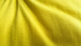 Pretty yellow cotton fabric background. Wrinkle yellow cotton fabric background for plain design with text or other objects stock photo