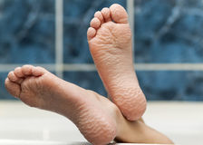 Wrinkled bare feet coming out from a bathtub. Young person getti Stock Image