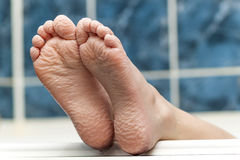 Wrinkled bare feet coming out from a bathtub. Young person getti. Ng a bath feet close-up indoor in bathroom interrior photo Stock Photo
