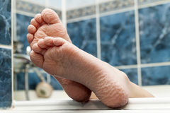 Wrinkled bare feet coming out from a bathtub. Young person getti Stock Photo