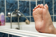 Wrinkled bare feet coming out from a bathtub. Young person getti. Ng a bath feet close-up indoor in bathroom interrior photo Royalty Free Stock Photography