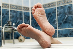 Wrinkled bare feet coming out from a bathtub. Young person getti. Ng a bath feet close-up indoor in bathroom interrior photo Royalty Free Stock Photos