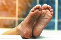 Wrinkled bare feet coming out from a bathtub. Young person getti. Ng a bath feet close-up indoor in bathroom interrior photo Royalty Free Stock Image