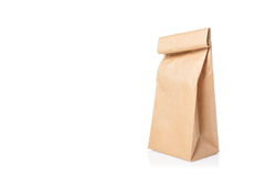 Wrinkled brown paper bag with folded top on isolated white backg. Round and light shadow reflection on ground, room for copyspace Stock Images