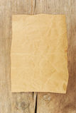 Wrinkled brown paper on wood. Old wrinkled brown paper on rustic wood stock photo