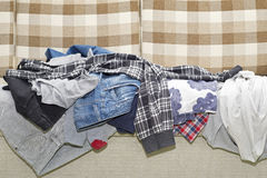 Wrinkled clothes lying on sofa Royalty Free Stock Photography