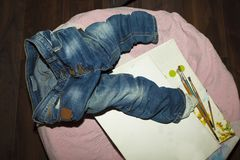 Wrinkled crumpled jeans carelessly thrown on the floor near a canvas. And brushes Stock Image