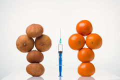 Wrinkled dried, smooth elastic tangerines in a female form and the syringe. Wrinkled dried and smooth elastic tangerines in the form of a figure of the person Stock Photos