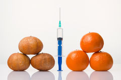 Wrinkled dried and smooth elastic tangerines the syringe. Wrinkled dried and smooth elastic tangerines and the syringe between them stock photo