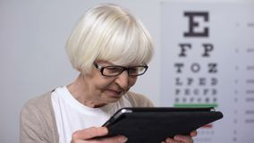Wrinkled elderly woman holding tab and trying to read, unhappy with poor sight stock video footage