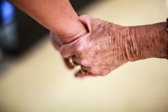 Wrinkled elderly woman`s hand holding to young man`s hand, walking in shopping mall.Family Relation, Health, Help, Support concept. Wrinkled elderly woman`s hand Royalty Free Stock Photography