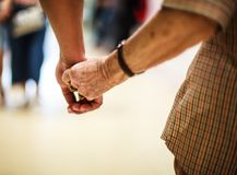 Wrinkled elderly woman`s hand holding to young man`s hand, walking in shopping mall.Family Relation, Health, Help, Support concept. Wrinkled elderly woman`s hand Stock Photography