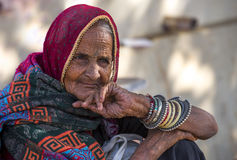 A wrinkled face lady. Waiting for bus in bus stop near pushkar, Rajasthan, India Stock Image