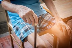 Wrinkled hand of old senior man with a cane stick Stock Photo