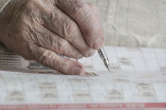 Wrinkled hand solving puzzle stock photography