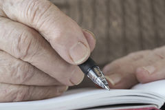 Wrinkled hand writing note with pencil. Closeup of a wrinkled hand writing note with pencil on notebook Royalty Free Stock Images
