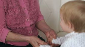 Wrinkled hands of an old grandma hold arms a child stock video footage