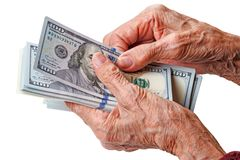 Hands of an old woman with dollars. Wrinkled hands of an old woman counts one hundred dollar bills Royalty Free Stock Images