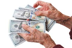 Old woman with dollars. Wrinkled hands of an old woman counts one hundred dollar bills Stock Photos