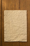 Wrinkled note paper on wood Stock Photography