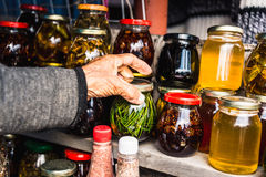 Wrinkled old female hands hold jar with Homemade jam from coniferous leaves Stock Photography