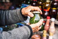 Wrinkled old female hands hold jar with Homemade jam from coniferous leaves Royalty Free Stock Image