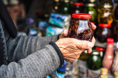 Wrinkled old female hands hold jar with jam Royalty Free Stock Photography