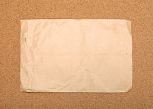 Wrinkled paper on corvkboard. Wrinkled brown envelope attached to cork board. As backdrop or background Stock Image