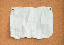 Wrinkled paper with green pins on cork board Stock Images