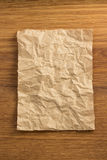 Wrinkled paper  on wood Stock Images