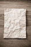 Wrinkled paper  on wood Stock Image
